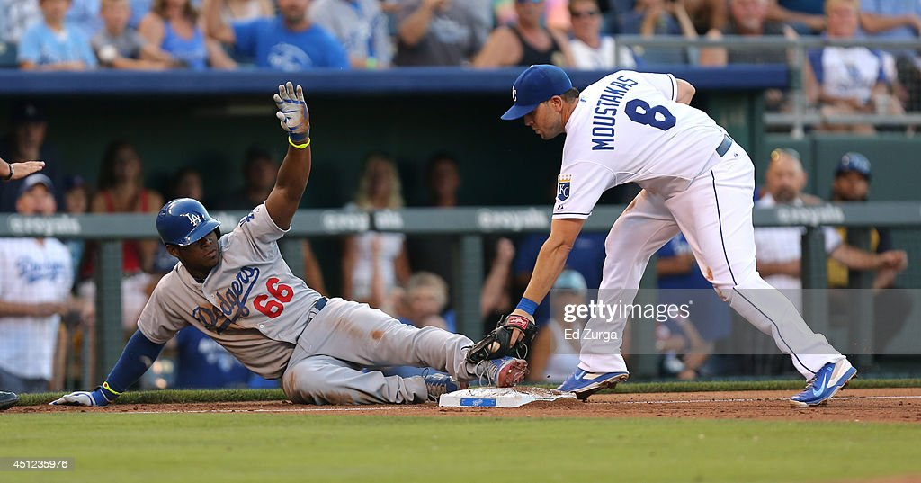 Yasiel Puig of the Los Angeles Dodgers slides into third for a triple past the tag of Mike Moustakas of the Kansas City Royals in the third inning at...