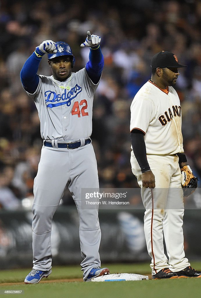 <a gi-track='captionPersonalityLinkClicked' href=/galleries/search?phrase=Yasiel+Puig&family=editorial&specificpeople=10484087 ng-click='$event.stopPropagation()'>Yasiel Puig</a> of the Los Angeles Dodgers stands on thirs base and celebrates after hitting a triple as Pablo Sandoval of the San Francisco Giants looks on in the top of the eighth inning at AT&T Park on April 15, 2014 in San Francisco, California. All uniformed team members are wearing jersey number 42 in honor of Jackie Robinson Day.