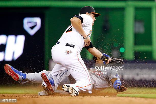 Yasiel Puig of the Los Angeles Dodgers steals second base under the tag of Derek Dietrich of the Miami Marlins during the eighth inning of the game...