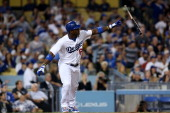Yasiel Puig of the Los Angeles Dodgers throws his bat as he watches his RBI double to break a 11 tie in the seventh inning against the San Francisco...