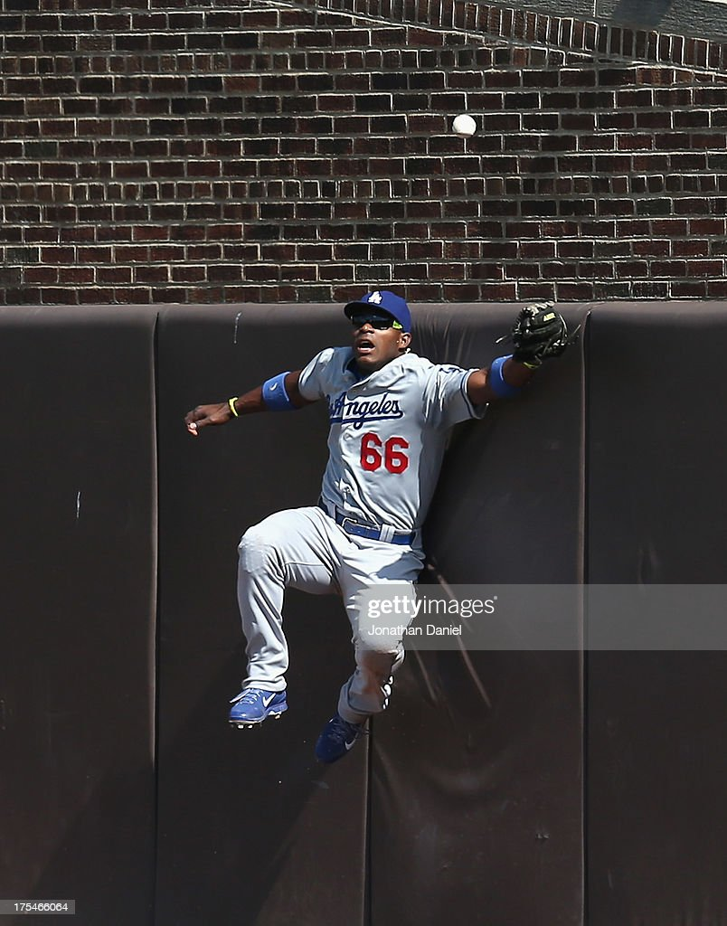 <a gi-track='captionPersonalityLinkClicked' href=/galleries/search?phrase=Yasiel+Puig&family=editorial&specificpeople=10484087 ng-click='$event.stopPropagation()'>Yasiel Puig</a> #66 of the Los Angeles Dodgers tries to catch a ball hit by Jeff Samardzija of the Chicago Cubs in the 4th inning at Wrigley Field on August 3, 2013 in Chicago, Illinois. The Dodgers defeated the Cubs 3-0.