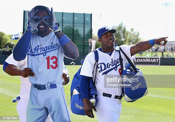 Yasiel Puig of the Los Angeles Dodgers walks alongside Juan Uribe as he carries a life size photo of Hanley Ramirez before the spring training game...