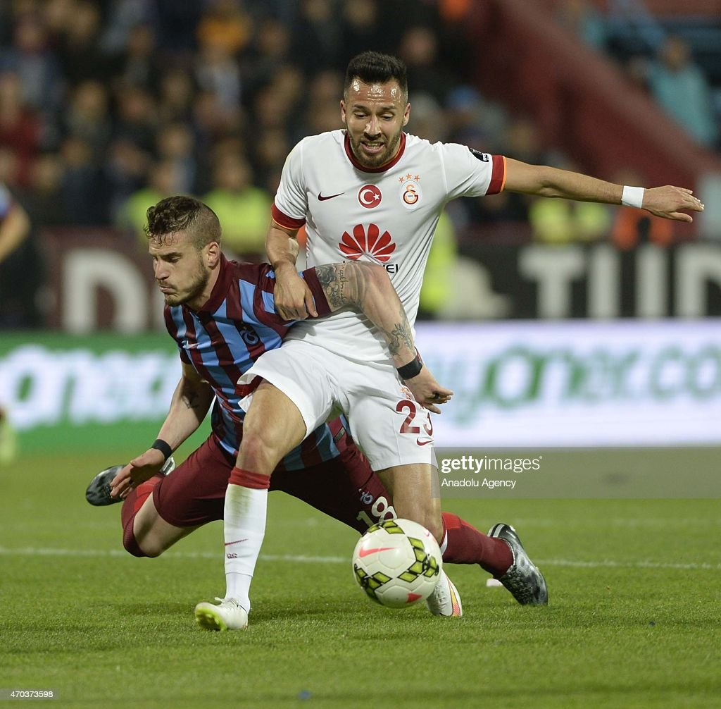 Yasin Oztekin (R) of Galatasaray in action against Deniz Yilmaz (L) of Trabzonspor during the Turkish Spor Toto Super League soccer match between Trabzonspor and Galatasaray at Avni Aker Stadium in Turkey on April 19, 2015.