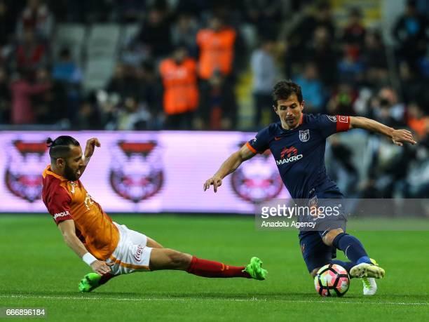 Yasin Oztekin of Galatasaray in action against Emre Belozoglu of Medipol Basaksehir during the Turkish Spor Toto Super Lig football match between...