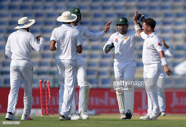 Yasir Shah and Sarfraz Ahmed of Pakistan celebrate taking the wicket of Dimuth Karunaratne of Sri Lanka during Day One of the First Test between...
