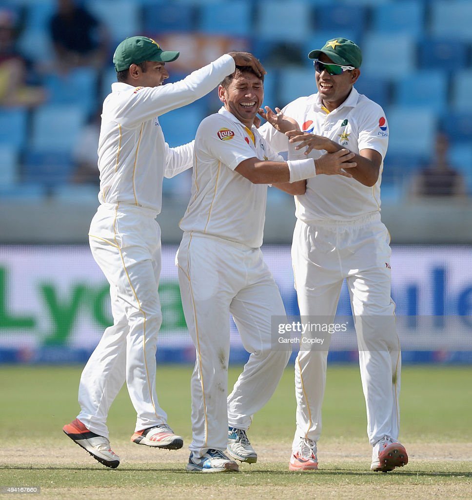 Yasir Shah of Pakistan celebrates with Asad Shafiq and Zulfiqar Babar after dismissing England captain Alastair Cook during day four of the 2nd test match between Pakistan and England at Dubai Cricket Stadium on October 25, 2015 in Dubai, United Arab Emirates.