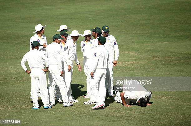 Yasir Shah of Pakistan drops to his knees to prey after dismissing Steve Smith of Australia during day three of the First Test between Pakistan and...
