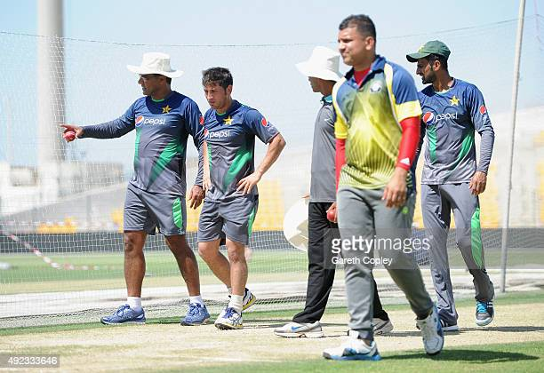 Yasir Shah of Pakistan leaves the nets alongside coach Waqar Younis after picking up an injury during a nets session at Zayed Cricket Stadium on...