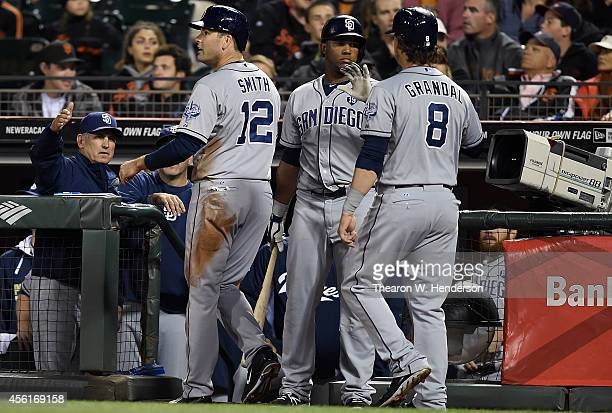Yasmani Grandal and Seth Smith of the San Diego Padres is congratulated by Rymer Liriano and manager Bud Black after Grandal and Smith both scored...