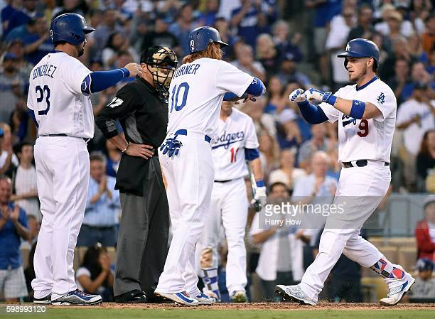 Yasmani Grandal of the Los Angeles Dodgers celebrates his three run homerun to take a 40 lead over the San Diego Padres with Justin Turner and Adrian...
