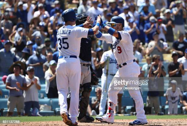 Yasmani Grandal of the Los Angeles Dodgers celebrates his tworun home run at homeplate with teammate Cody Bellinger during the fourth inning of the...