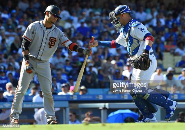 Yasmani Grandal of the Los Angeles Dodgers hands Gorkys Hernandez of the San Francisco Giants his bat after it flew out of his hands on a swing in...