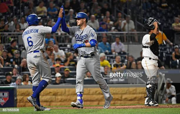 Yasmani Grandal of the Los Angeles Dodgers is greeted by Curtis Granderson after hitting a two run home run in the seventh inning during the game...