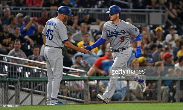 Yasmani Grandal of the Los Angeles Dodgers is greeted by third base coach Chris Woodward as he rounds the bases after hitting a two run home run in...