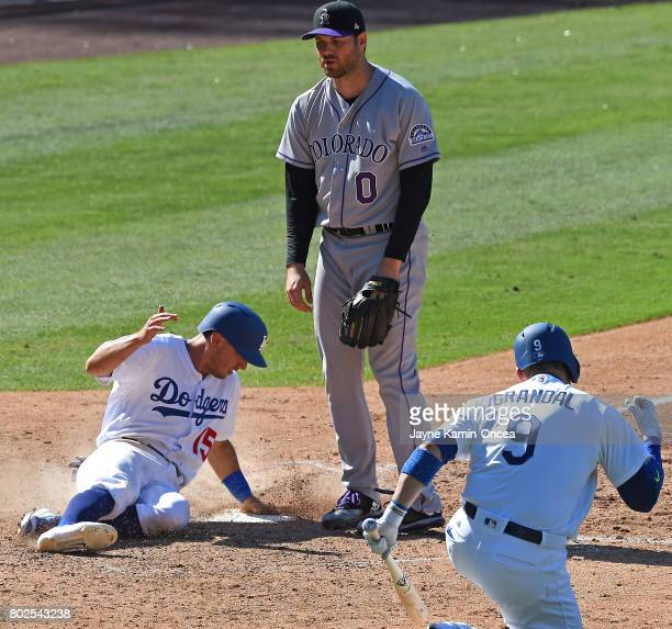 Yasmani Grandal of the Los Angeles Dodgers pumps his fist as Austin Barnes of the Los Angeles Dodgers scores the go ahead run after a wild pitch by...