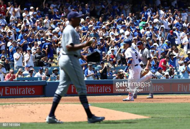Yasmani Grandal of the Los Angeles Dodgers rounds third base as Cory Spangenberg of the San Diego Padres looks on after Grandal hit a tworun home run...