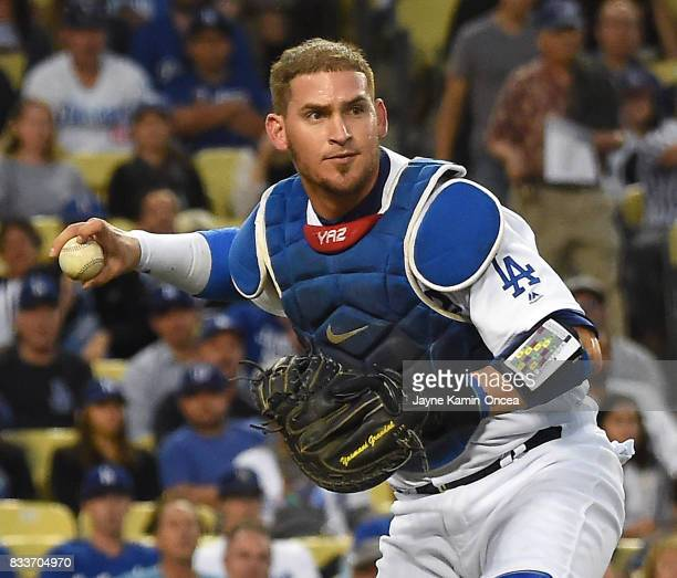 Yasmani Grandal of the Los Angeles Dodgers throws a runner out at first base during the game against the Chicago White Sox at Dodger Stadium on...