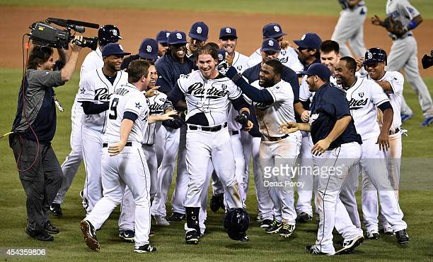 Yasmani Grandal of the San Diego Padres center is mobbed by teammates after hitting a walk off single during the twelfth inning of a baseball game...
