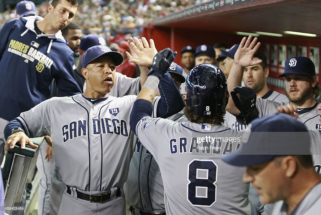 Yasmani Grandal #8 of the San Diego Padres is congratulated by bench coach Dave Roberts #10 (L) and teammates after his solo home run against the Arizona Diamondbacks during the fourth inning of a MLB game at Chase Field on September 13, 2014 in Phoenix, Arizona.