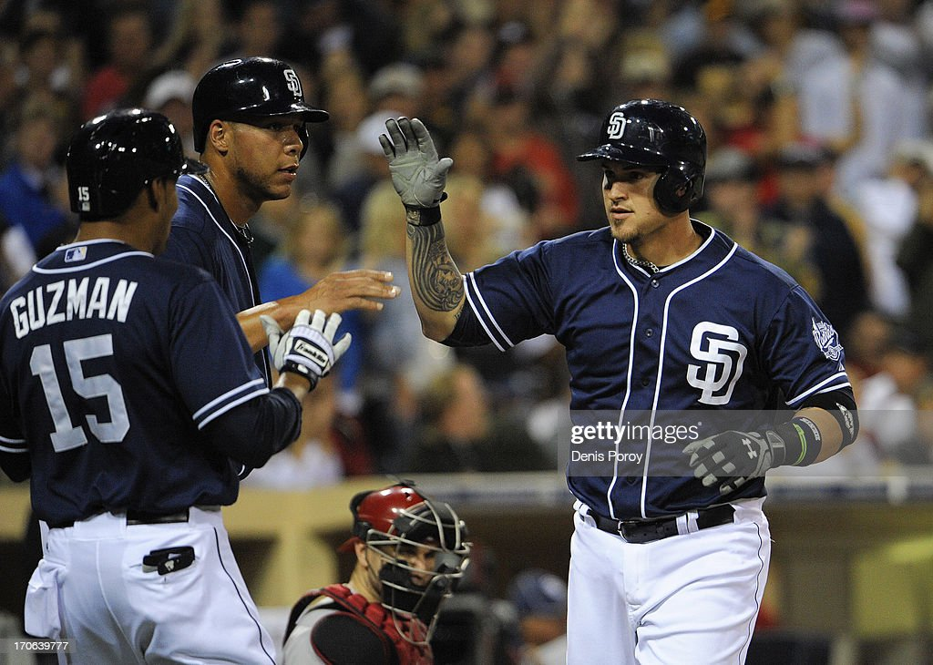 Yasmani Grandal #12 of the San Diego Padres, right, is congratulated by Kyle Blanks #88, center, and Jesus Guzman #15, left, after hitting a three-run homer in the fourth inning of a baseball game against the Arizona Diamondbacks at Petco Park on June 15, 2013 in San Diego, California.