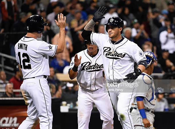 Yasmani Grandal of the San Diego Padres right is congratulated by Seth Smith after hitting a three run home run during the sixth inning of a baseball...