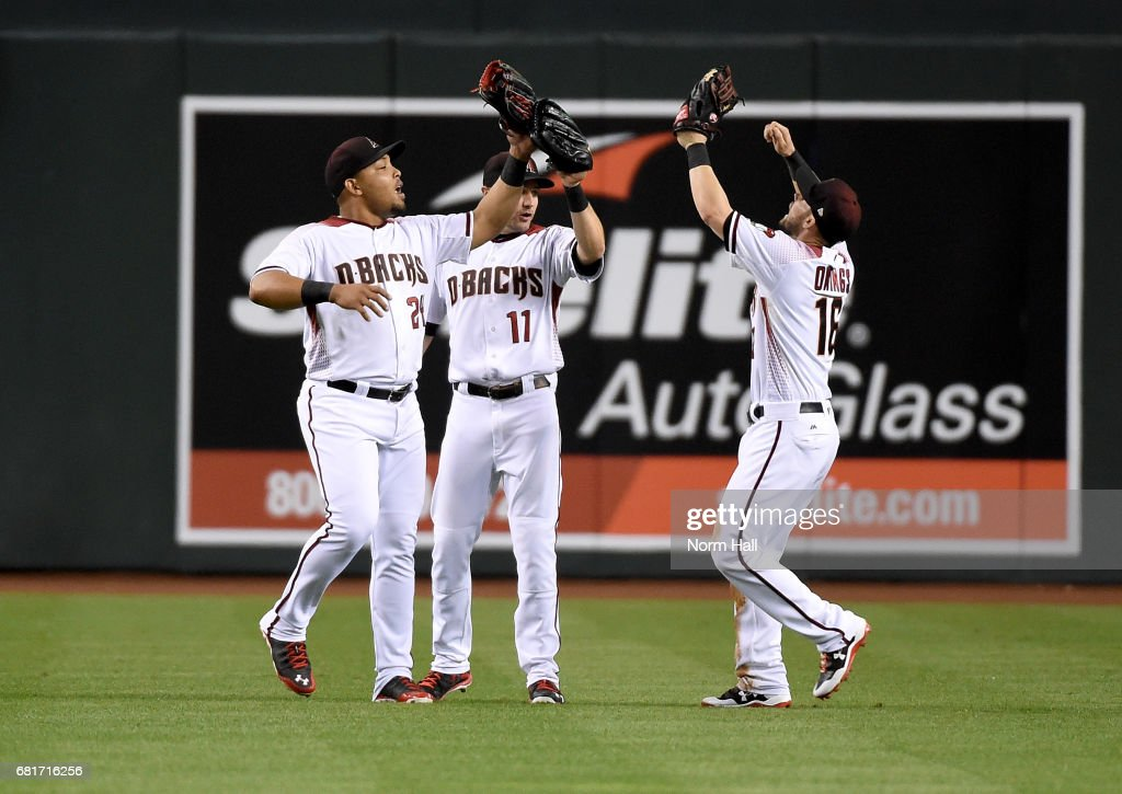 Yasmany Tomas #24, AJ Pollock #11 and Chris Owings #16 of the Arizona Diamondbacks celebrate a 7-1 win against the Detroit Tigers at Chase Field on May 10, 2017 in Phoenix, Arizona.