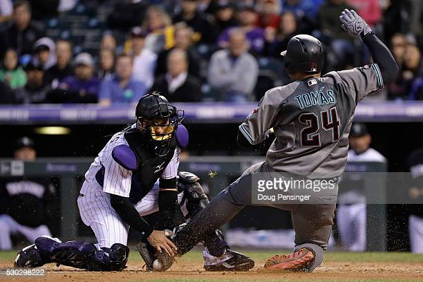 Yasmany Tomas of the Arizona Diamondbacks is tagged out at the plate by catcher Tony Wolters of the Colorado Rockies while trying to score on a...