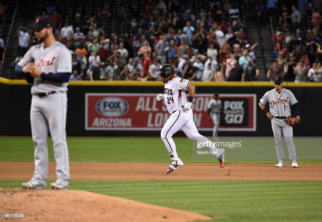Yasmany Tomas #24 of the Arizona Diamondbacks rounds the bases after hitting a two-run home run off of Anibal Sanchez #19 of the Detroit Tigers as Jose Iglesias #1 looks on during the seventh inning at Chase Field on May 10, 2017 in Phoenix, Arizona.