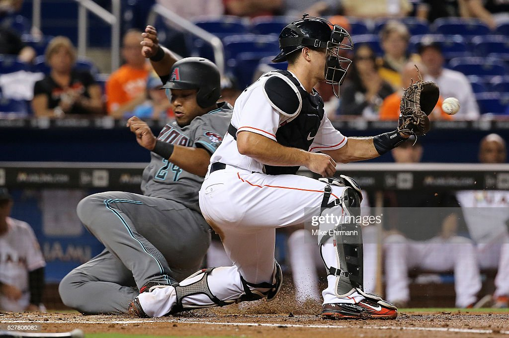 Yasmany Tomas #24 of the Arizona Diamondbacks slides home past the tag of <a gi-track='captionPersonalityLinkClicked' href=/galleries/search?phrase=J.T.+Realmuto&family=editorial&specificpeople=10507745 ng-click='$event.stopPropagation()'>J.T. Realmuto</a> #11 of the Miami Marlins during a game at Marlins Park on May 3, 2016 in Miami, Florida.