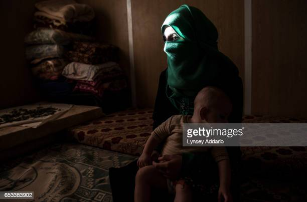 Yasmeen poses for a portrait with her baby months after leaving her abusive husband and returning home to live with her family at the Zaatari refugee...