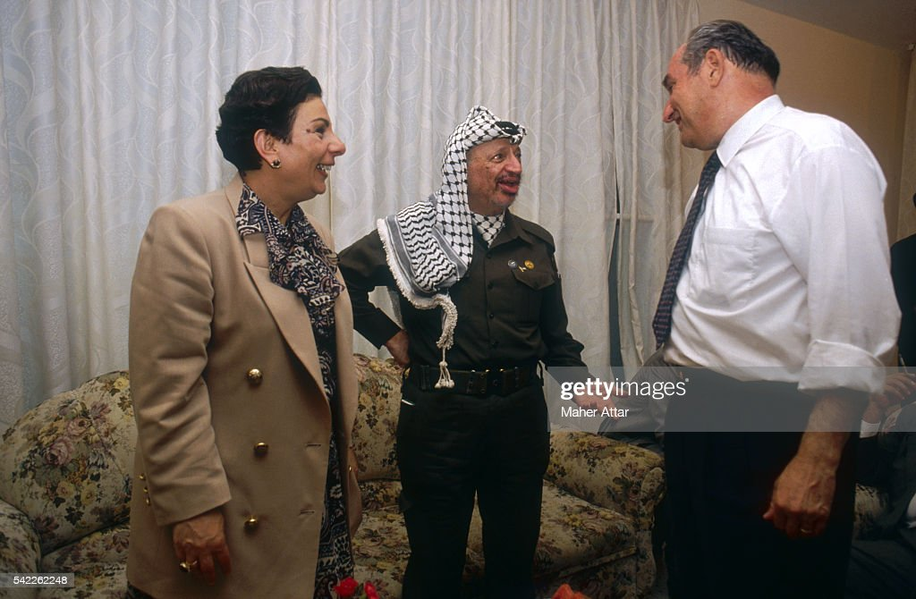 <a gi-track='captionPersonalityLinkClicked' href=/galleries/search?phrase=Yasser+Arafat+-+Political+Figure&family=editorial&specificpeople=118625 ng-click='$event.stopPropagation()'>Yasser Arafat</a> (center) celebrates his return to Gaza with Hanane Ashraoui (left) and Faical Husseini (right). Ashraoui is the spokesperson for the PLO and Husseini is a member of the PLO Executive Committee in charge of Jerusalem affairs.