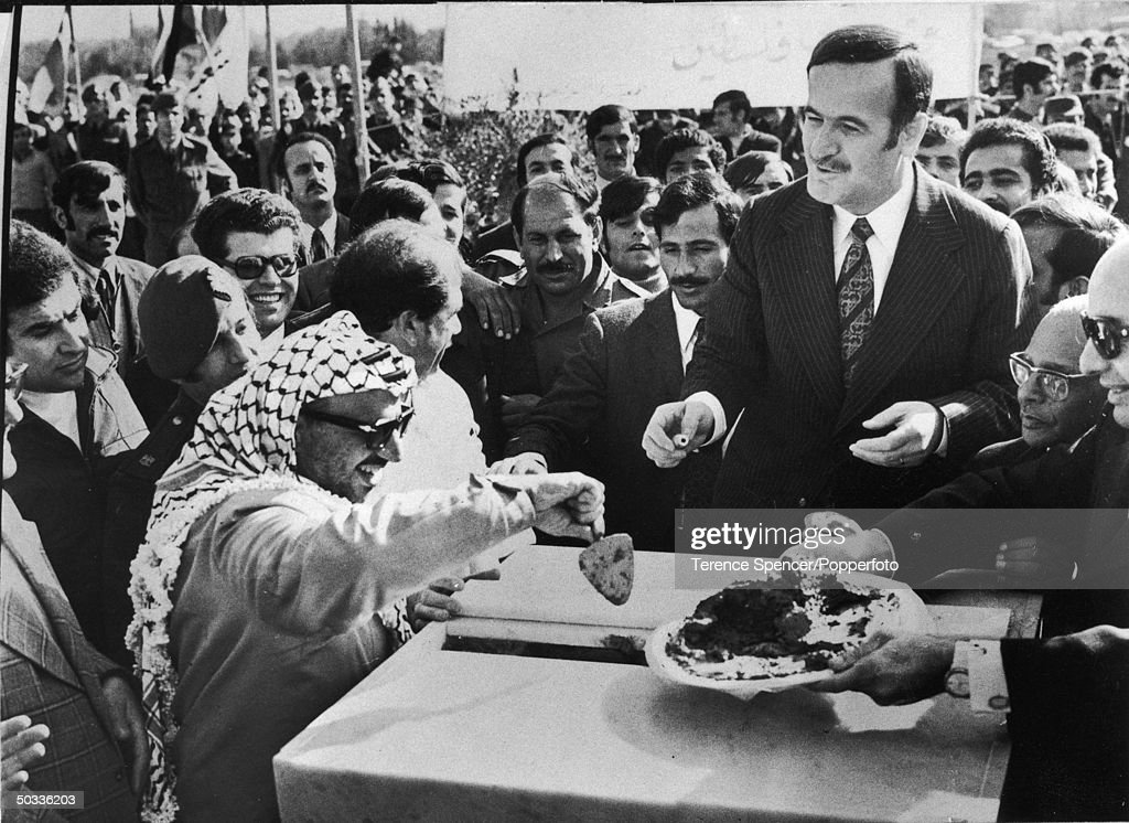 PLO leader Yasser Arafat (L) w. Syrian Pres. Hafez Assad (R) appearing convivial at crowd-framed event.