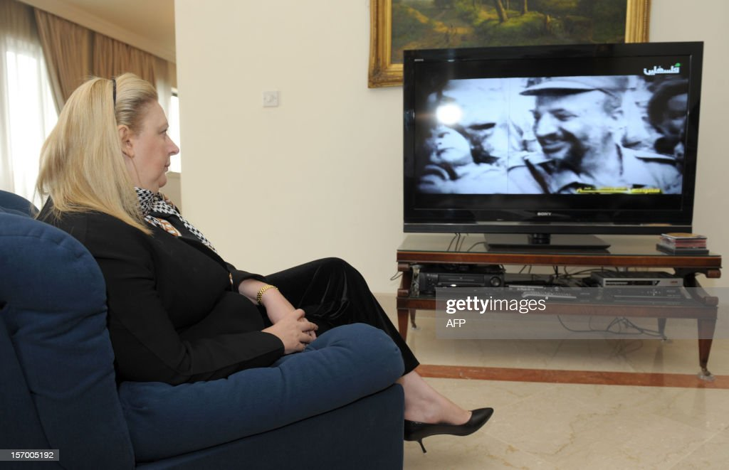 Yasser Arafat's widow, Suha Arafat, watches the television reports of the exhumation of her husband at her home in Sliema in Malta on November 27, 2012. The remains of iconic Palestinian leader Yasser Arafat were exhumed on Tuesday, eight years after his death, with experts set to test for signs that he was poisoned. AFP PHOTO / MATTHEW MIRABELLI