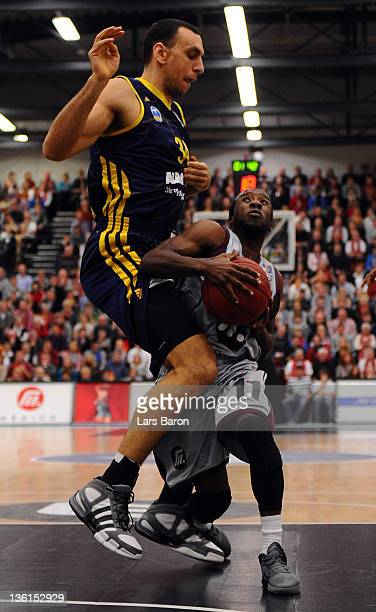 Yassin Idbihi of Berlin challenges David Holston of Artland during the Beko Basketball Bundesliga match between Artland Dragons Quakenbrueck and Alba...