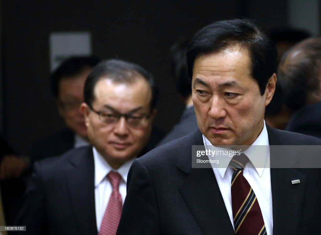 Yasuhiro Sato, president and chief executive officer of Mizuho Financial Group Inc., right, arrives for a news conference in Tokyo, Japan, on Tuesday, Feb. 26, 2013. Mizuho Financial Group Inc., Japan's third-biggest bank by market value, plans to cut an additional 600 jobs as it targets profit of 550 billion yen ($6 billion) in three years following the merger of its lending units. Photographer: Tomohiro Ohsumi/Bloomberg via Getty Images