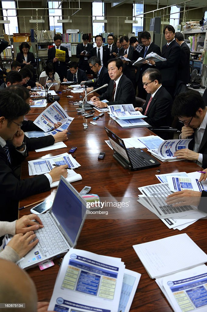 Yasuhiro Sato, president and chief executive officer of Mizuho Financial Group Inc., third from right, speaks during a news conference in Tokyo, Japan, on Tuesday, Feb. 26, 2013. Mizuho Financial Group Inc., Japan's third-biggest bank by market value, plans to cut an additional 600 jobs as it targets profit of 550 billion yen ($6 billion) in three years following the merger of its lending units. Photographer: Tomohiro Ohsumi/Bloomberg via Getty Images