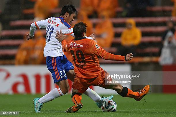 Yasuhiro Yamamoto of Albirex Niigata and Dejan Jakovic of Shimizu SPulse compete for the ball during the JLeague match between Shimizu SPulse and...