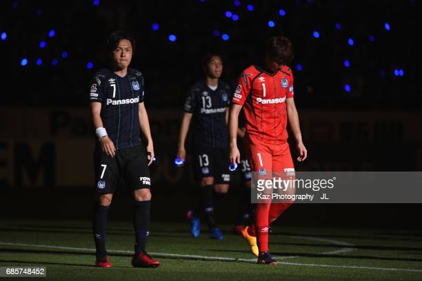 Yasuhito Endo and Masaaki Higashiguchi of Gamba Osaka leave the pitch after their 30 victory in the JLeague J1 match between Gamba Osaka and Sagan...