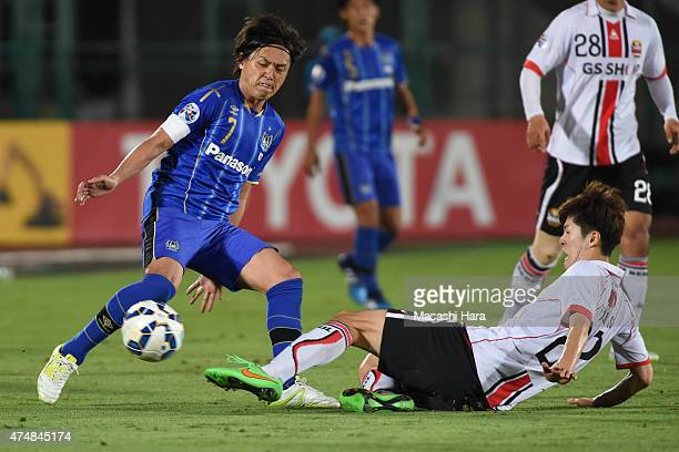 Yasuhito Endo of Gamba Osaka and Koh Myongjin of FC Seoul compete for the ball during the AFC Champions League Round of 16 match between Gamba Osaka...