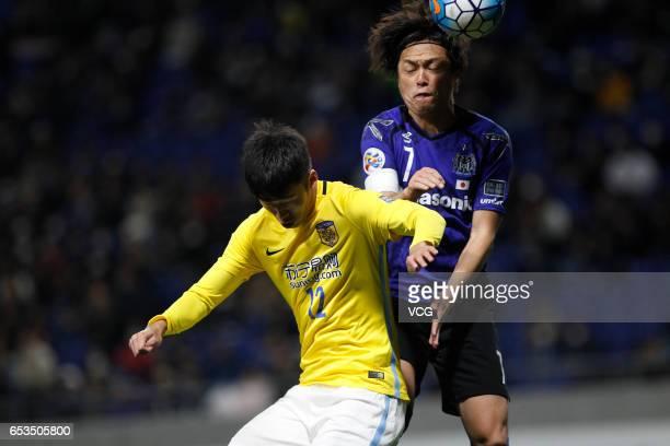 Yasuhito Endo of Gamba Osaka and Zhang Xiaobin of Jiangsu Suning compete for the ball during the AFC Champions League Group H match between Gamba...