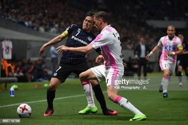 Yasuhito Endo of Gamba Osaka controls the ball under pressure of Franco Sbuttoni of Sagan Tosu during the JLeague J1 match between Gamba Osaka and...