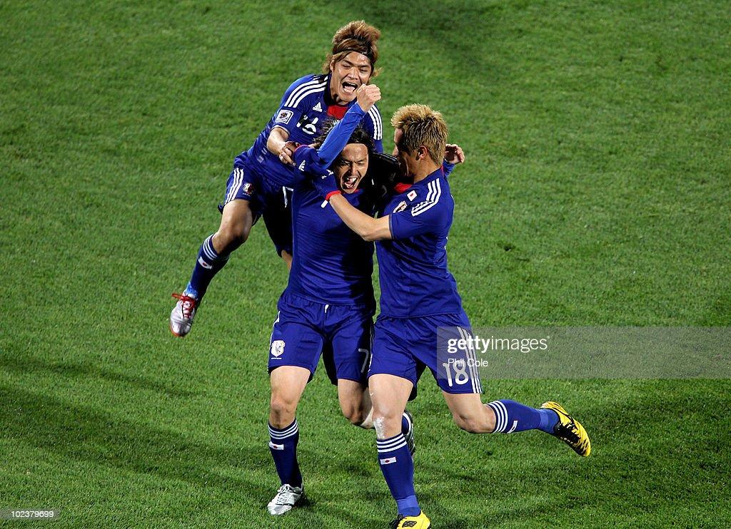Yasuhito Endo of Japan celebrates scoring his team's second goal from a free kick with Yoshito Okubo and Keisuke Honda of Japan during the 2010 FIFA...