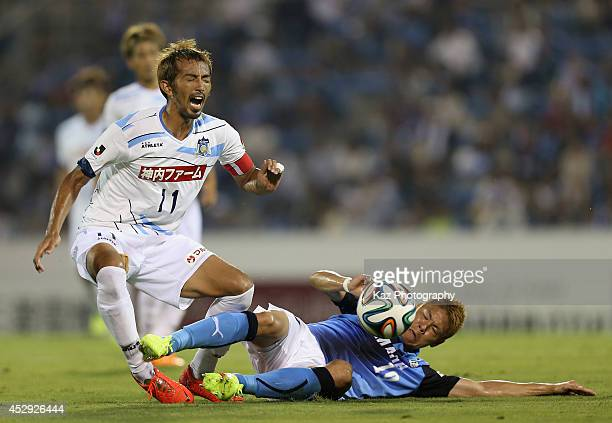 Yasumasa Nishino of Kamatamare Sanuki is tackled by Masahiko Inoha of Jubilo Iwata during the J League second division match between Jubilo Iwata and...