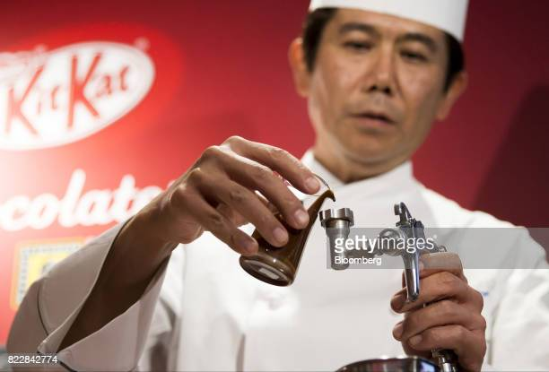 Yasumasa Takagi owner and head chef of Le Patissier Takagi pours liquid chocolate into an airbrush during a media preview of the KitKat Chocolatory...
