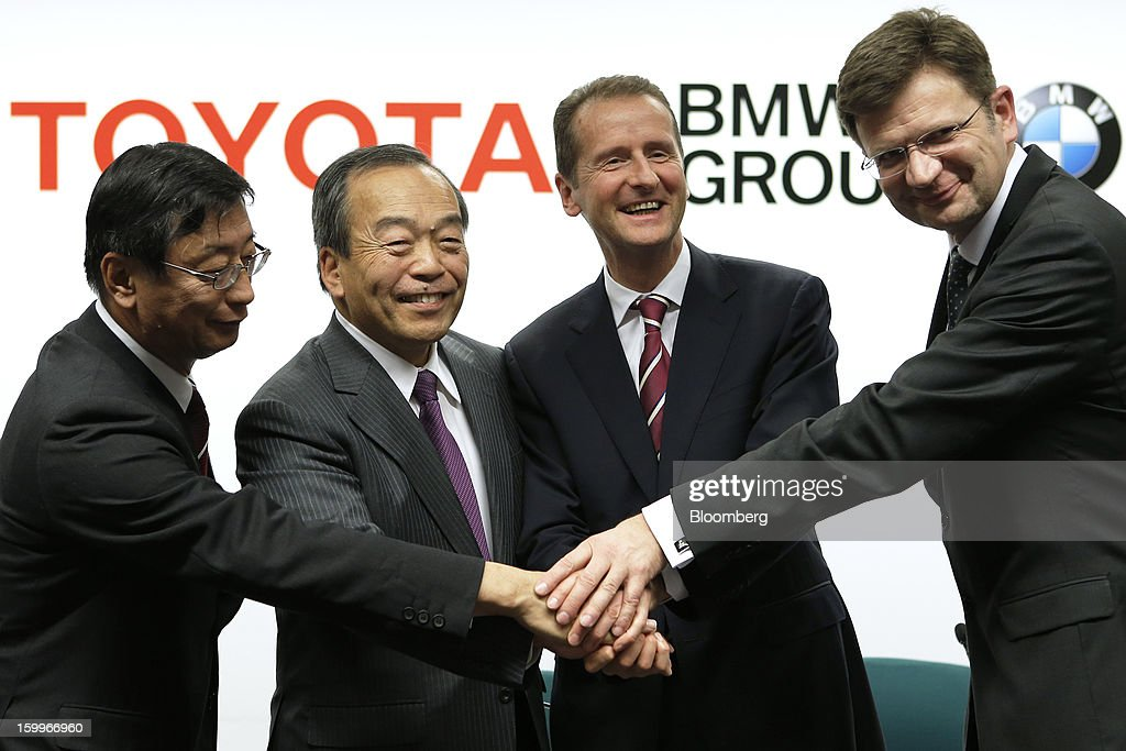 Yasumori Ihara, director and senior managing officer at Toyota Motor Corp., from left, Takeshi Uchiyamada, vice chairman of Toyota Motor Corp., Herbert Diess, development chief of Bayerische Motoren Werke AG (BMW), and Klaus Froehlich, senior vice president at BMW Group, shake hands as they pose for a photograph during a joint news conference in Nagoya, Aichi Prefecture, Japan, on Thursday, Jan. 24, 2013. Toyota, the world's biggest maker of gasoline-electric hybrid vehicles, signed a binding agreement with BMW to jointly develop fuel-cell systems for cars. Photographer: Kiyoshi Ota/Bloomberg via Getty Images