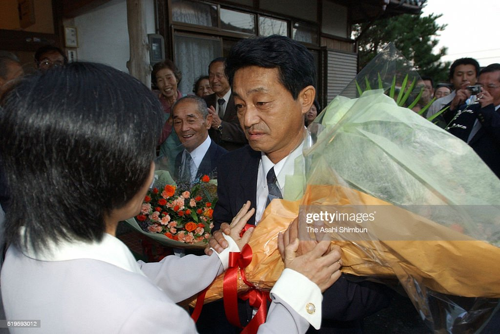 Yasushi Chimura receives a flower bunches on arrival at his home on October 17 2002 in Obama Fukui Japan