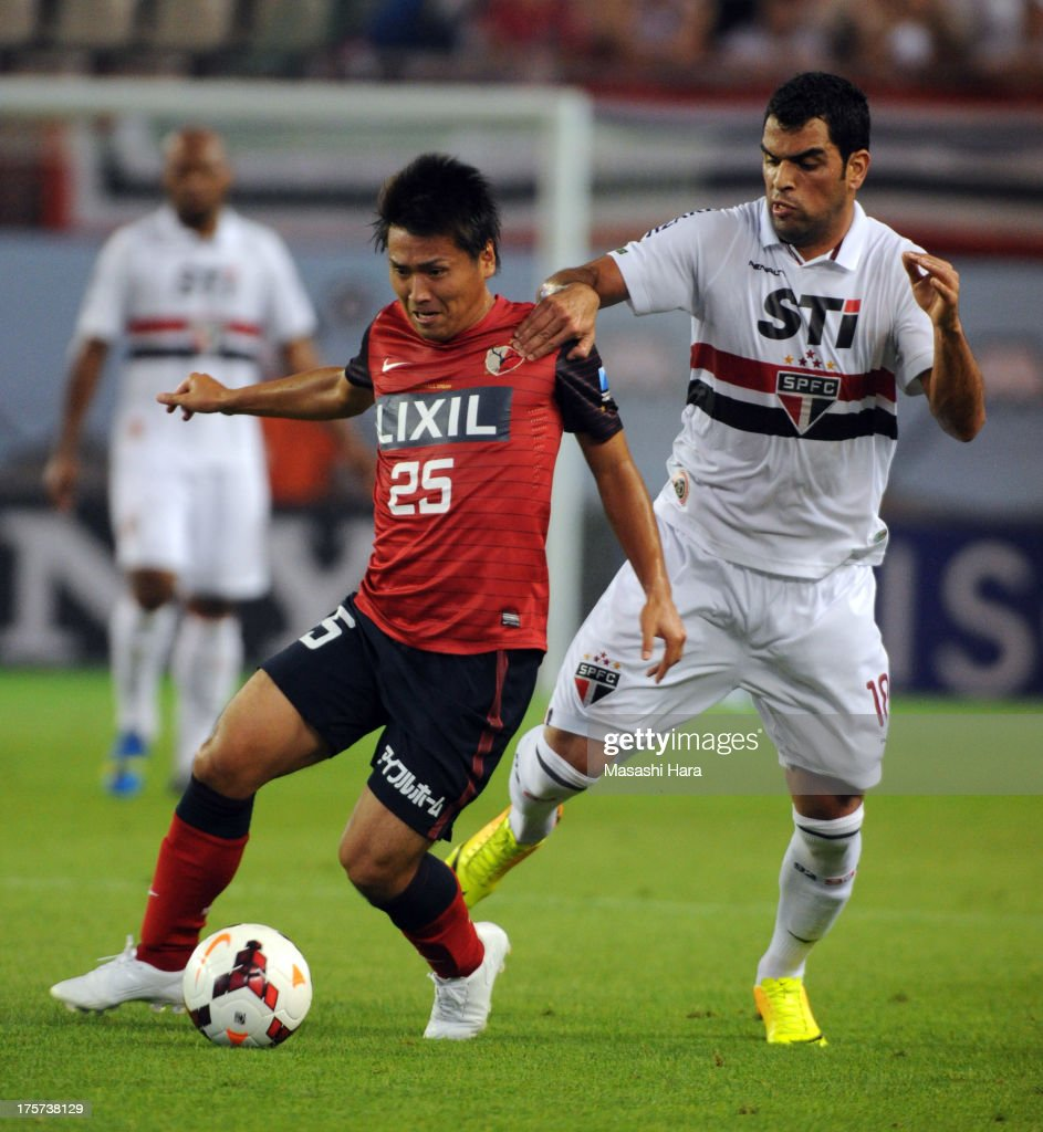 Yasushi Endo #25 of Kashima Antlers (L) and Maicon #18 of Sao Paulo FC compete for the ball during the Suruga Bank Championship match between Kashima Antlers and Sao Paulo FC at Kashima Soccer Stadium Stadium on August 7, 2013 in Kashima, Ibaraki, Japan.