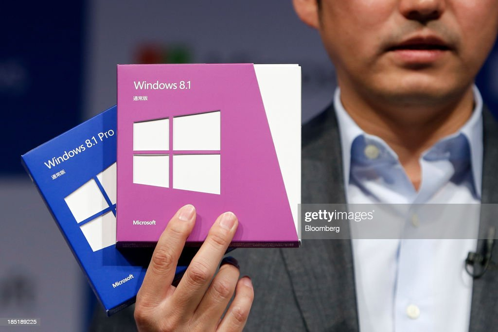 Yasushi Fujimoto, director at Microsoft Japan Co., displays packages of Microsoft Corp.'s Windows 8.1 operating system during a launch event in Tokyo, Japan, on Friday, Oct. 18, 2013. Microsoft Chief Executive Officer Steve Ballmer, who will be retiring within a year, said the company is still working to make sure that the personal computer remains relevant as 'the device of choice.' Photographer: Kiyoshi Ota/Bloomberg via Getty Images