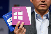 Yasushi Fujimoto director at Microsoft Japan Co displays packages of Microsoft Corp's Windows 81 operating system during a launch event in Tokyo...