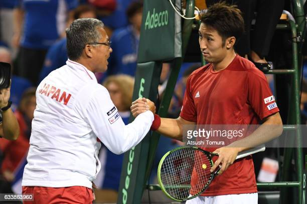 Yasutaka Uchiyama of Japan and team captain of Japan Minoru Ueda celebrate after winning the match against PierreHugues Herbert of France during the...